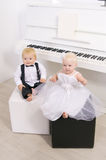 Boy and girl sitting at piano Royalty Free Stock Images