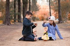 Boy and girl playing in the park with rag dolls royalty free stock image