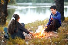 Boy and girl sitting on the river Bank, make a fire, autumn forest at sunset, beautiful nature and reflection of trees in the wate. R royalty free stock photography