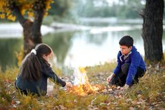 Boy and girl sitting on the river Bank, make a fire, autumn forest at sunset, beautiful nature and reflection of trees in the wate. R royalty free stock images