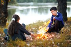 Boy and girl sitting on the river Bank, make a fire, autumn forest at sunset, beautiful nature and reflection of trees in the wate. R stock images