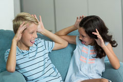 Boy and girl sitting on sofa teasing each other in living room. At home royalty free stock photography