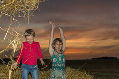 Boy and girl sitting on a stack of straw Stock Photo
