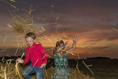 Boy and girl sitting on a stack of straw Royalty Free Stock Image