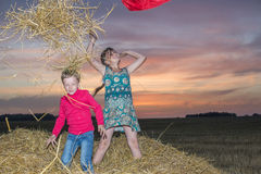 Boy and girl sitting on a stack of straw Royalty Free Stock Photo