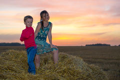 Boy and girl sitting on a stack of straw Stock Images