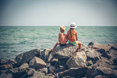 Boy and girl sitting on the stone in sea Stock Photography