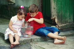 Boy and girl sitting on the street with a fish in a jar .Brother and sister see fish in the aquarium. Stock Photos