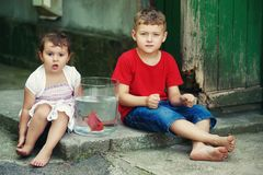 Boy and girl sitting on the street with a fish in a jar .Brother and sister see fish in the aquarium. Royalty Free Stock Photo