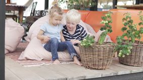 Cute brother and little sister hugging on a beautiful veranda in summer stock video footage