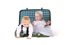 Boy and a girl sitting in a suitcase Royalty Free Stock Photos
