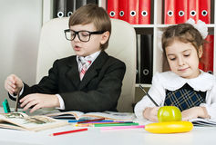 Boy and girl sitting at a table in the school royalty free stock images