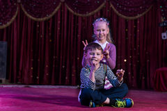 Boy and Girl Sitting Together on Stage Royalty Free Stock Photo