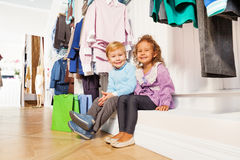 Boy and girl sitting under hangers with clothes Royalty Free Stock Photo