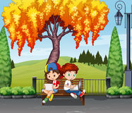 Boy and girl sitting under the tree Royalty Free Stock Images