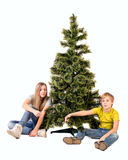 Boy and girl sitting under the tree and point the finger Royalty Free Stock Photography