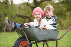 Boy And Girl Sitting In Wheelbarrow Royalty Free Stock Images