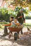 Boy and girl (7-9) sitting in wheelbarrow in garden, grandmother collecting autumn leaves, smiling, portrait Royalty Free Stock Photography