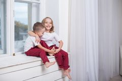 Boy and girl sitting on the windowsill looking out the window royalty free stock images
