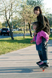 Boy and girl on skateboard Royalty Free Stock Images