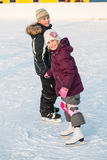 Boy and girl skating on rink hand in hand in winter. Focus on a girl royalty free stock image