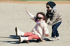 Boy and girl skating on the street Stock Images