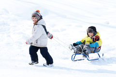 Boy and girl with sled. Little happy girl taking sled with little joyful boy, winter time Royalty Free Stock Photos