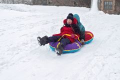 Boy and girl sledding from the mountain. emotional joyful and long-standing brother and sister spend together in winter. Boy and girl sledding from the mountain royalty free stock photos