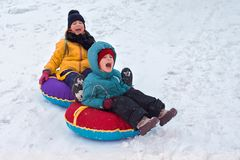 Boy and girl sledding from the mountain. emotional joyful and long-standing brother and sister spend together in winter stock photography