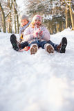Boy And Girl Sledging Through Snowy Woodland Royalty Free Stock Photography