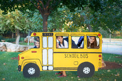 Boy and girl in small school bus. Photography play - kids in a cardboard miniature school bus in a city park royalty free stock photography