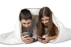 Boy and girl with smart phones under blanket Stock Photography