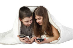 Boy and girl with smart phones under blanket Stock Photo