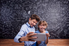 Boy and girl  with smartphone, taking selfie, against blackboard Royalty Free Stock Photo