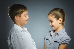 Boy and girl are smiling at each other. Portrait children isolated on grey. Boy and girl are smiling at each other. Portrait children smiling isolated on grey Royalty Free Stock Photos
