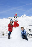 Boy and girl (6-8) by snowman in snow field, smiling, portrait, mountain range in background Royalty Free Stock Image