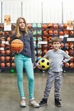 Boy and girl with soccer ball and basketball in store Royalty Free Stock Image