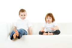 Boy and girl on sofa Stock Photos