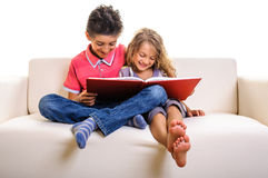 Boy and girl on sofa with big red book Stock Photos