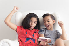 Boy and girl on the sofa playing on mobile Stock Photos