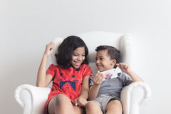 Boy and girl on the sofa playing on mobile Stock Photo
