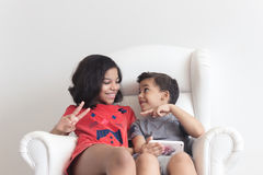 Boy and girl on the sofa playing on mobile Royalty Free Stock Images