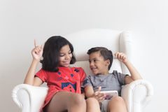 Boy and girl on the sofa playing on mobile Royalty Free Stock Image