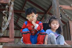 Boy and girl in spider man suit and worry. Boy look worrier in spider man suit with his sister Royalty Free Stock Image