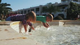 Boy and girl splash in fountain.summer time stock video