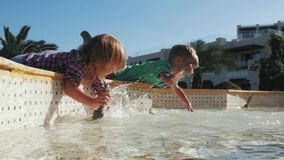 Boy and girl splash in fountain.summer time stock video footage