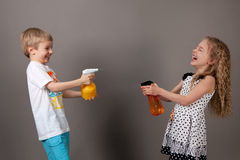 Boy and girl squirting water Stock Images