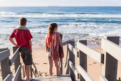 Boy Girl Stairs Beach Waves. Teen boy girl unidentified standing on beach stairway steps early morning watching looking at ocean waves and reefs stock image