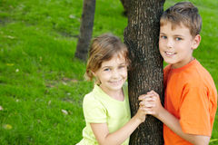 Boy and girl stand on each side of tree Royalty Free Stock Image