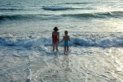 Boy and girl stand holding hands in the water on the beach Royalty Free Stock Image